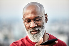 Bald Man With White Beard Talking Through Mobile Phone At Building Terrace During Sunset