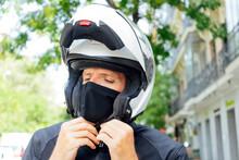 Male Biker Putting On Helmet