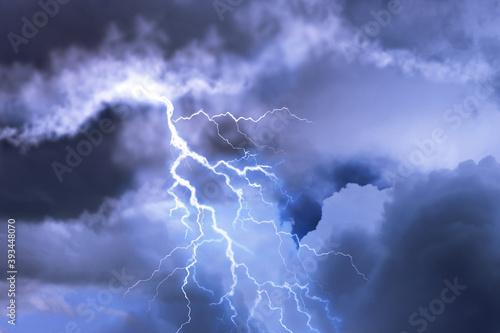 Lightning in dark cloudy sky during thunderstorm Fototapeta