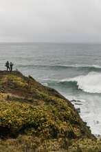 Two People Standing On An Overlook At The Coast Watching Waves From A Storm