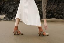 Person Wearing Long White Skirt Reaching Down Toward Shoe On The Beach