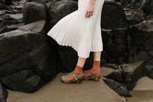 Young Person Wearing Flowing White Skirt And Orange Socks Standing In Front Of Dark Rocks