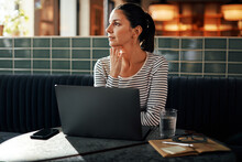 Young Businesswoman Sitting At A Table Thinking About Work