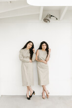 Two Women Wearing Matching Outfits With White Background And Same Body Language