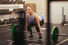 Fit Young Woman Lifting Heavy Weights In A Gym