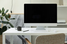 Modern Desktop Computer And Coffee Mug On White Desk In Creative Space