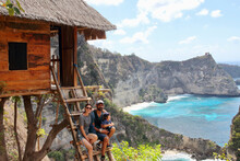 Parents And Little Kid Enjoying The Views From The Wooden Stairs Of One Of The Famous Treehouses In Thousand Islands Viewpoint, On Of The Most Amazing Spots In Nusa Penida Island, Indonesia, Bali.