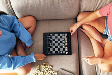 Two Sisters Playing Chess Together On Their Living Room Sofa
