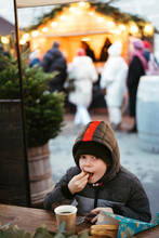 A Young Boy At A Street Christmas Market.