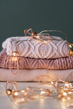 A Stack Of Knitted Sweaters With Fairy Lights Garland..