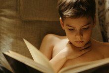 A Young Boy Reads A Book.