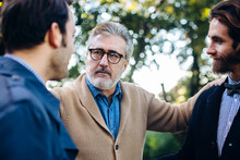 Senior Man Supporting Adult Sons In Garden