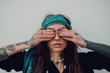 Trendy Adult Woman With Ethnic Makeup And Piercing Covering Eyes