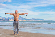 Focused Bearded Man Working Out With Elastic Bands On Coast