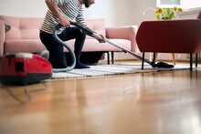 Crop Man Cleaning Carpet At Home