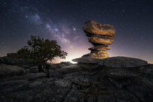 Tree And Rock Formation Against Night Sky
