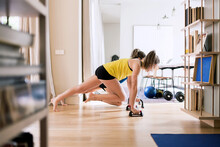 Sportswomen Doing Plank With Grips At Home