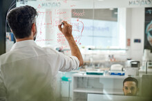 Unrecognizable Worker Writing Graphs On Glass Wall In Laboratory