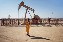 Ethnic Woman Standing On Oil Field