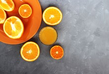 Bright Citrus Fruits In An Orange Plate And A Glass Of Juice On A Gray Background. Useful Vitamins.