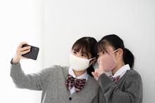 スマートフォンで自撮りをするマスクをつけた女子学生2人