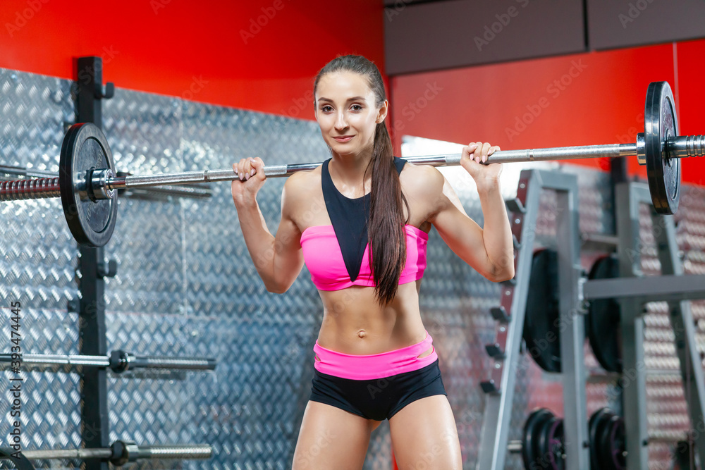 Fototapeta Photo of a happy muscular woman holding a barbell on her shoulders ready to do exercises in gym