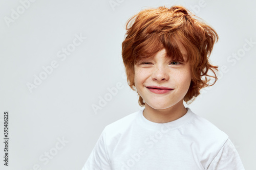 Canvastavla Sly red-haired boy with narrowed eyes conceived something bad white t-shirt crop