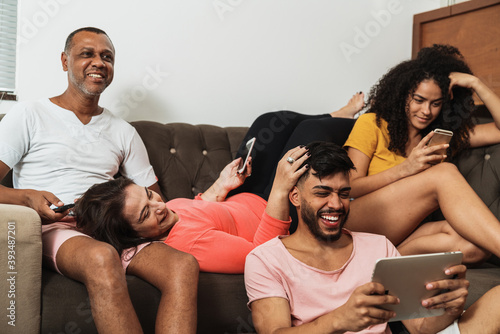Obraz na plátne Latin American family sitting on the couch, using technology