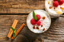 Glass Cups Of Tasty Rice Pudding With Raspberry And Raisins On Wooden Table