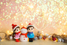 Winter New Year Image With Toy Figures Of A Girl, Boy And Snowman. Christmas Background With Sparkles, Lights And Bokeh