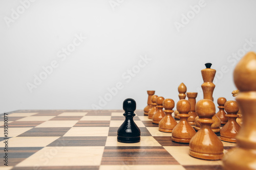 Fototapeta premium Chessboard with wooden figures against grey background