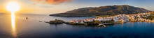 Sunrise View Of The Idyllic Town Of Andros Island, Cyclades, Greece, Set On Rocks Reaching Out Into The Calm Sea With The Fortress And Lighthouse At The Very Top