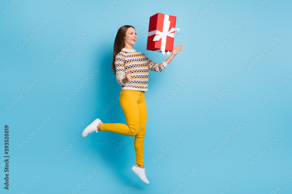 Fototapeta Full length photo of childish young woman dressed ornament pullover throwing big gift isolated blue color background