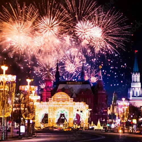 Festive salute and fireworks on the red square in Moscow. Salute lights over the Kremlin and GUM at the New Year celebration. Multicolored salute for Christmas in Moscow at night, Russia #393532270