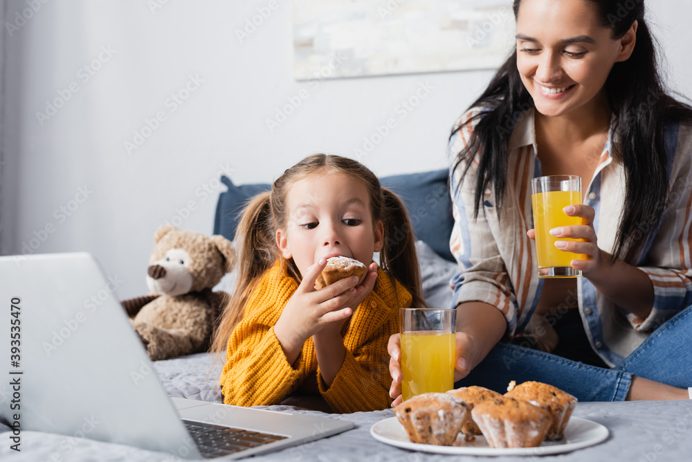 Fototapeta girl eating muffin near cheerful mother while watching movie on laptop