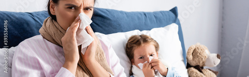 Tela ill child and mother with runny nose sneezing in paper napkins, banner