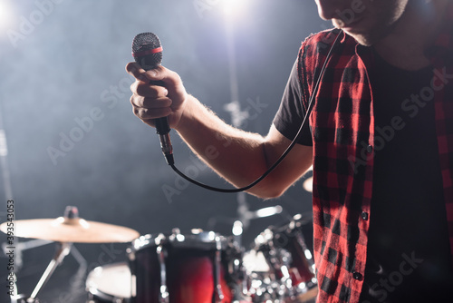 Cropped view of vocalist with microphone with blurred drum kit on background Fotobehang