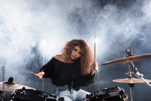Female musician with drumsticks playing on drum kit while looking at camera with Canvas