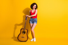 Full Length Body Size Photo Of Smiling Girl With Curly Hair Posing Holding Keeping Guitar At Country Students Party Isolated On Vivid Yellow Color Background