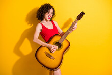 Portrait Photo Of Funky Girl With Curly Hair Singing Loudly Holding Keeping Playing Performing Music On Acoustic Guitar At Party Isolated On Vivid Yellow Color Background