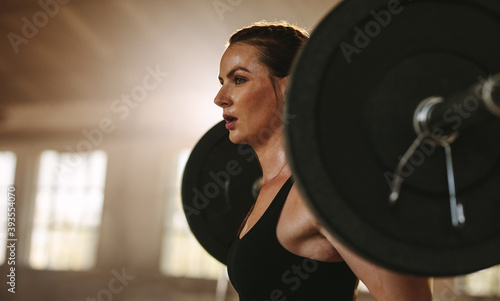 Fototapeta Woman exercising back squats with a barbell obraz