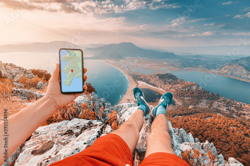 Obraz Young and sportive man on top of a mountain with a stunning view of the Iztuzu beach in Turkey and the sea coast looks into a smartphone with a map app for navigation - fototapety do salonu