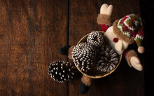 White-tipped Christmas Pine Cones In A Santa Claus Basket Arranged Over Rustic Wood, Top View.