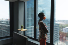 African American Woman Wearing Face Mask Looking Out Of The Window At Modern Office
