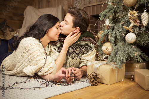 Beautiful brunette caucasian romantic loving couple in cozy warm sweaters in the cabin on a christmas new year eve, smiling, kissing, having fun with each other Fototapete