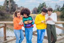 Group Of Multiethnic Friends Millennials Using Mobile Phones  Addicted To Viral Trends Following And Chatting Using Emoji And Emoticon