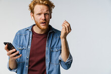 Confused Redhead Guy In Wireless Earphones Using Cellphone