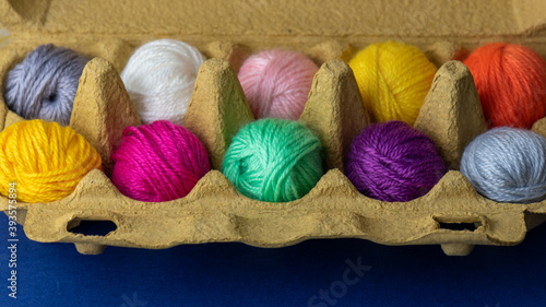 mini balls of colourful wool in an egg box Fotobehang
