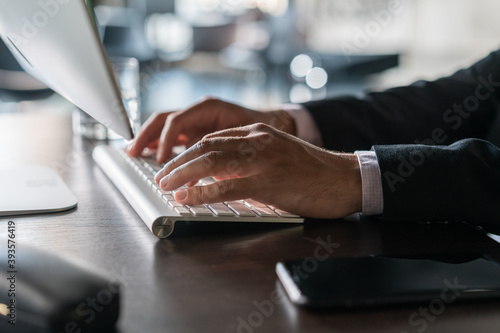 Office manager male hands typing on computer keyboard, closeup. Businessman working, typing on the wireless keyboard, no face, concept of office work
