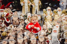 A Little Girl In A Red Suit Sitting Among New Year's Toys On A Shop Window Under The Christmas Tree. Toy Santa Claus, St. Nicholas, Gnomes And Ocharacters Look At An Interesting Little Girl With Tails